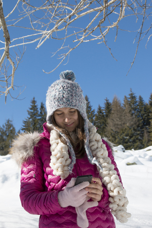 A young girl with a smartphone in the mountains in snowy winter Reklamní fotografie