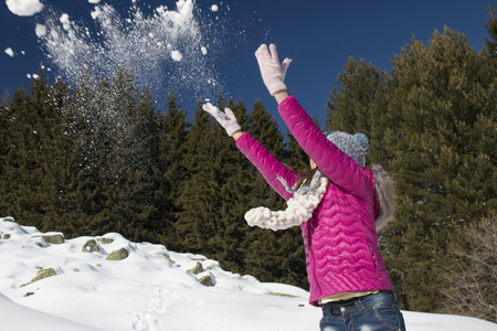 A young girl plays with snow in winter in the mountains