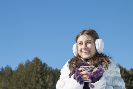 A young girl with a cup of hot tea in the mountains in winter