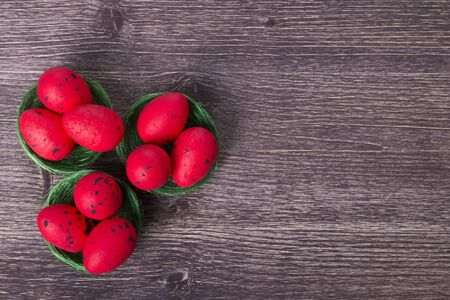 Red Easter eggs on green nest on a wooden table