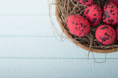 Red easter eggs and wooden bowl on blue background with copy space