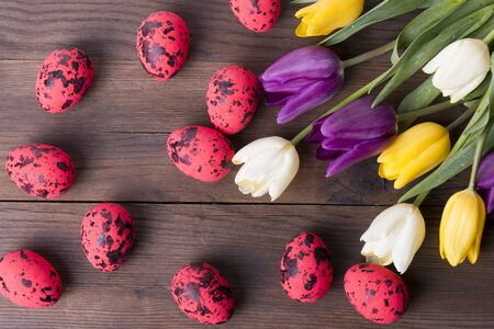Red Easter eggs and colorful tulips on a wooden table Reklamní fotografie
