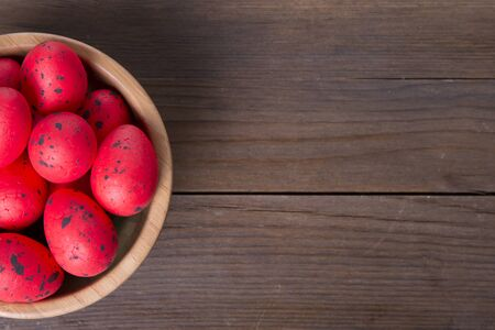 Red easter eggs and wooden bowl on wooden background with copy space
