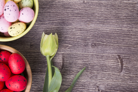 Colorful Easter eggs on bowl and tulip on a wooden table