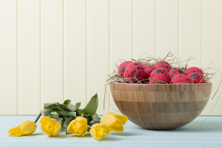 Easter background with red eggs and yellow tulips on yellow wall. Top view with copy space Reklamní fotografie