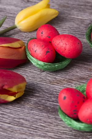 Red Easter eggs on green nest and colorful tulips on a wooden table