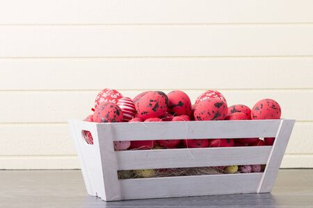 Red Easter eggs in a wooden container on a yellow background with copy space