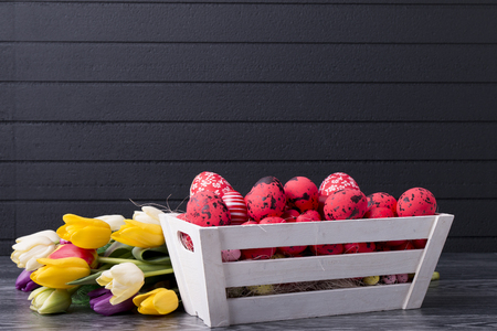 Red Easter eggs in a wooden container, bouquet of tulips on a black background with copy space