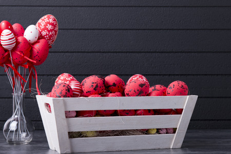 Red Easter eggs in a wooden container on a black background with copy space