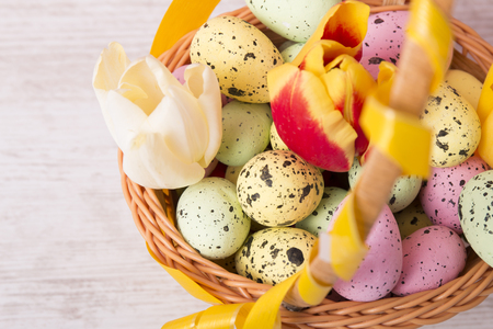 Colorful Easter eggs and tulips in basket on wooden background with copy space Reklamní fotografie