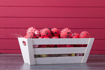 Red Easter eggs in a wooden container on a red background with copy space