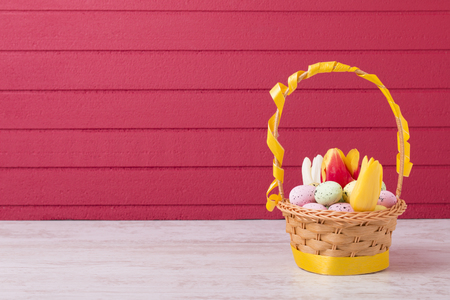 Colorful Easter eggs and tulips in basket on red background with copy space Reklamní fotografie