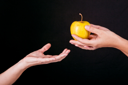female hands serving apple second female hands