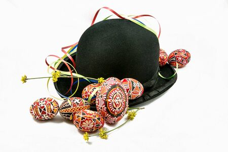 Easter eggs and bowler hat on white background