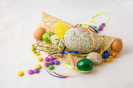 Stone and colored eggs on the white background