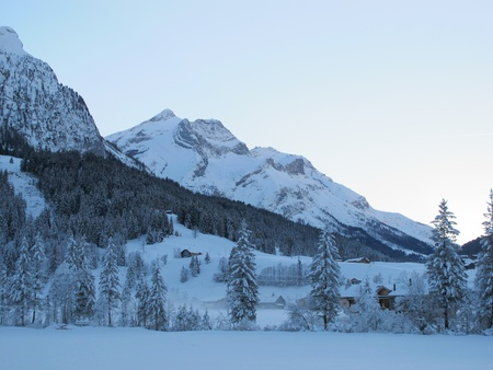saanenland: gsteig at gstaad in the evening light, winter cold