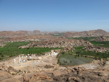 Little village near Hampi, India. Rice fields and granite mountains. photo