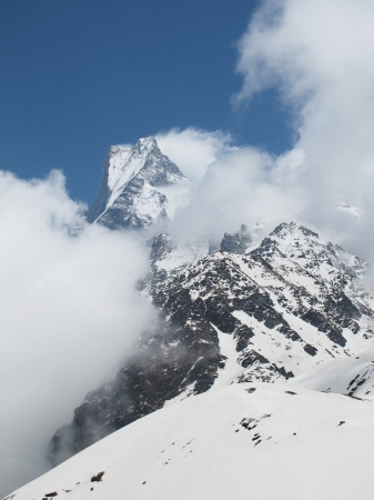 Peak of famous Machapuchare, Fish Tail mountain, surrounded by clouds photo