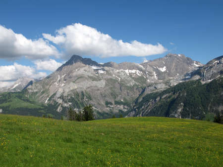 gsteig bei gstaad: Green meadow, mountains and clouds in the Swiss Alps Stock Photo