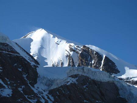 viento soplando: Viento que sopla nieve sobre una monta�a alta