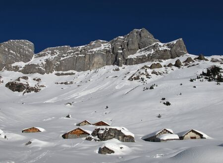 winter scenery: Idyllic winter scenery, snow covered huts and mountains
