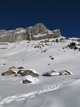 Snow covered huts and mountains near Braunwald photo