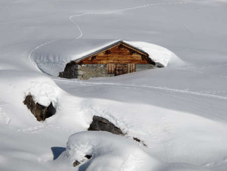 Timber hut nearly completely under the snow photo