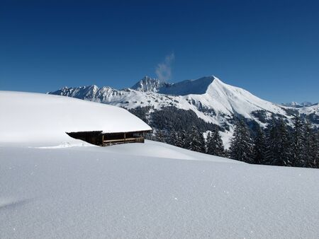 gstaad: Mountain named Lauenenhorn and snow covered hut