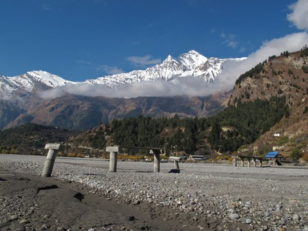 Ruined bridge and Dhaulagiri, scene in the Annapurna Conservation Area, Nepal Stock Photo
