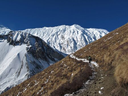 foot path: Foot path of the Tilicho Trek and snow covered Tilicho Peak Stock Photo