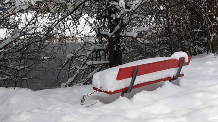 Red bench covered by deep snow photo