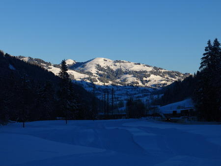 gstaad: First sunlight on the Rellerli, winter scene near Gstaad