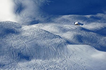 Ski and snowboard tracks and little hut photo