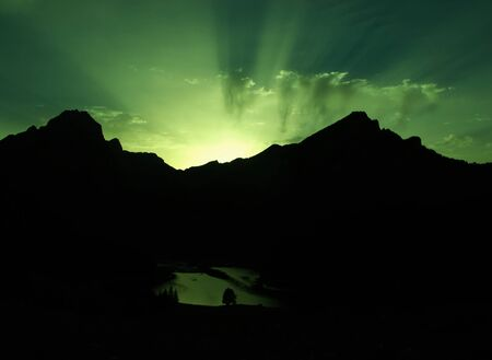 Fantasy landscape, sunbeams and green sky above a mountain and lake Stock Photo