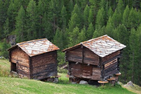 sheds: Traditional rural architecture in Zermatt, old timber sheds with stone roofs Stock Photo
