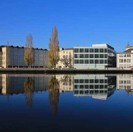 mirroring: Trees and buildings mirroring in the Rhine Stock Photo