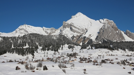 toggenburg: Snow covered Alpstein range and houses of the village Wildhaus Stock Photo