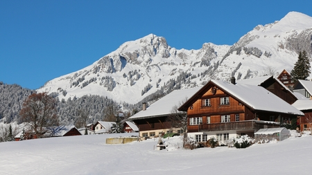 snow covered mountains: Farmhouse in the Swiss Alps and snow covered mountains Stock Photo