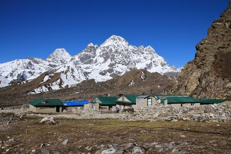 snow capped mountain: Lodges in Thagnak and snow capped mountain Stock Photo