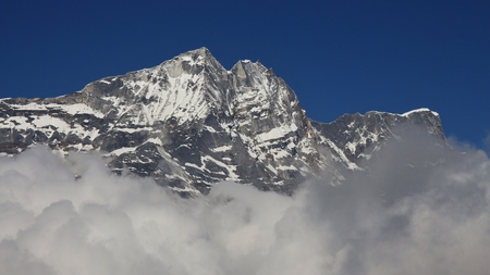reaching out: High mountain in the Himalayas reaching out of clouds Stock Photo
