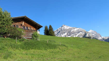 gsteig bei gstaad: Old farmhouse, green meadow and Mt Spitzhorn Stock Photo