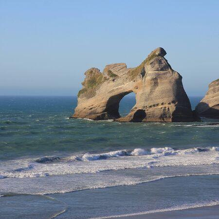 aotearoa: Island with a big hole at Wharariki Beach Stock Photo
