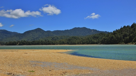 inlet: Landscape in the Abel Tasman national park. Awaroa Inlet. Sandy beach, blue water and green hills.