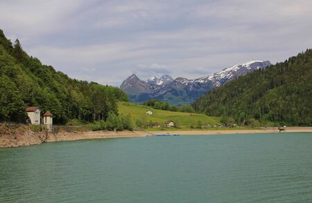 glarus: Landscape in the Swiss Alps. Springtime at Lake Kloental. Lake, forest and mountains.