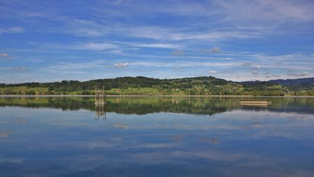 mirroring: Green hills mirroring in Lake Pfaffikon. Spring scene in Zurich Canton, Switzerland.