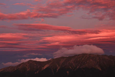 aotearoa: Colorful sky over a mountain range in New Zealand. View from Mt Robert.