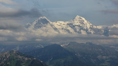 Snow capped mountains Eiger and monch on a cloudy summer day.