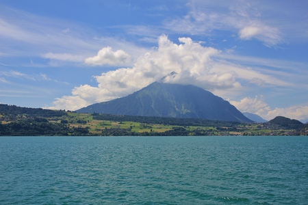canton berne: Summer scene in the Swiss Alps. Mt Niesen surrounded by clouds. Turquoise water of lake Thunersee.