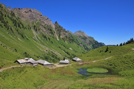 glarus: Rural scene in Glarus Canton. Huts and sheds on the Lachenalp. Pond and mountains.