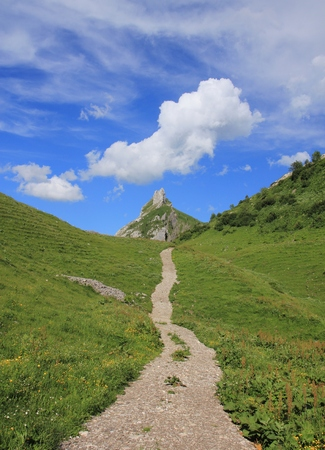 glarus: Summer scene in Glarus Canton, Swiss Alps. Hiking trail leading towards Mt Dejebstogg. Cloud. Stock Photo